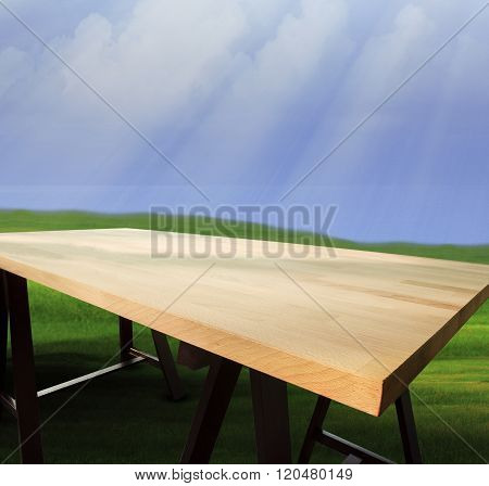 Top Of Empty Wood Table With Natural Green Grass Field And Blue Sun Light Sky Use As Multi Purpose B
