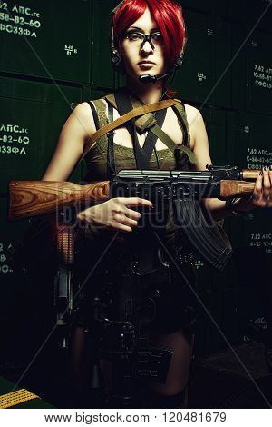 Armed redhead girl with automatic rifle posing in a storage ** Note: Visible grain at 100%, best at smaller sizes