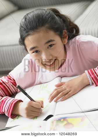 Portrait of young girl doing homework