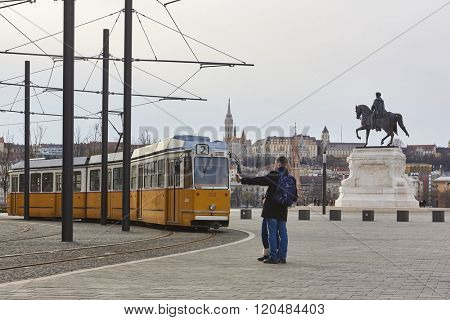 BUDAPEST, HUNGARY - FEBRUARY 02: Young couple taking selfie next to tram line number two near Hungarian Parliament building, with Fisherman's Bastion in the background. February 02, 2016 in Budapest.