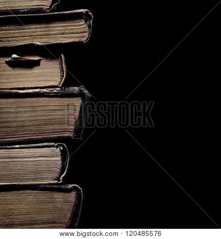 Stack Of Old Tattered Book On A Black Background