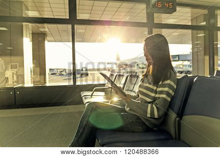Passenger traveler woman in airport use of tablet at departure hall