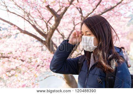 Woman suffer from Pollen allergy under sakura tree