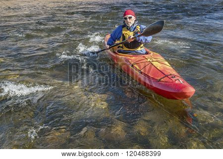 senior male paddler is paddling whitewater kayak on a turbulent river