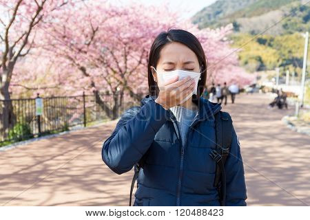 Woman feeling unwell with Pollen allergy under sakura tree