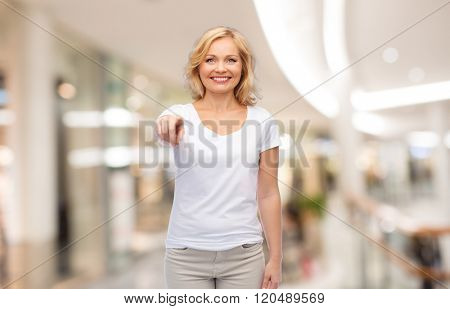 gesture, advertisement and people concept - smiling woman in blank white t-shirt pointing finger to you at shopping center or mall