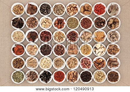 Chinese herbal medicine selection in white china bowls over hessian background.