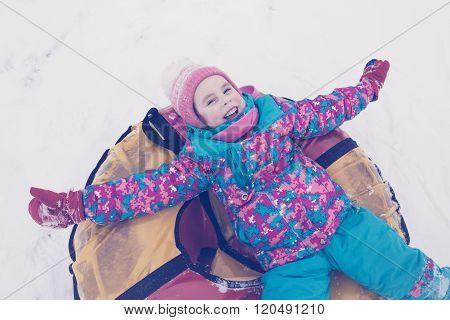 Cute kid riding snow tube winter day.