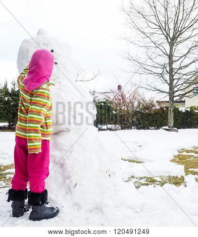 Girl Making Snowman In Garden, Hiding Under Pink Hat