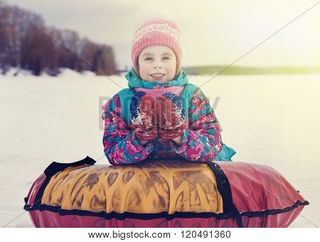 Cute kid riding snow tube winter day.
