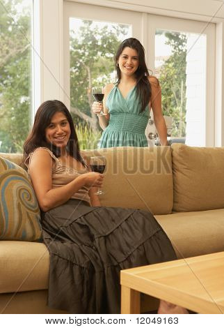 Portrait of two women in living room with wine glasses