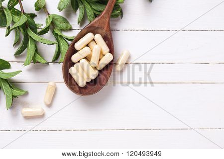 Fresh Leaves Of Herb And  Pills  In Spoon And On White Table.