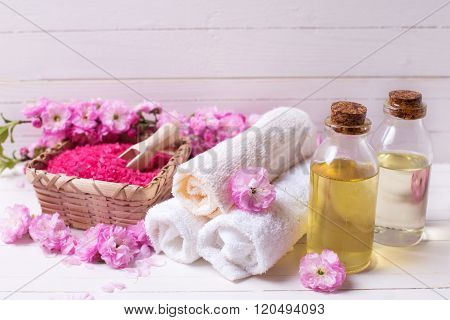 Pink Sea Salt In Bowl, Towels,  Bottles With Aroma Oils  And Pink Flowers