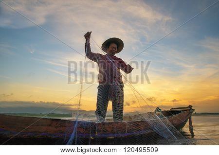 Fisherman fishing at lake in Morning Thailand.