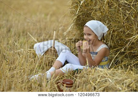 Girl with milk and fritter in field