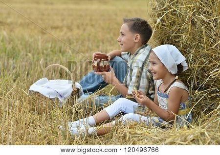 kids  with milk and fritters in field