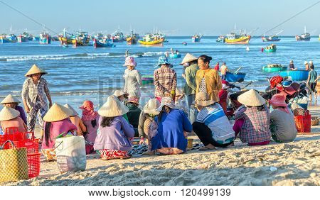 Women sit inside group fish market fishing port village