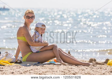 Young Mother Sitting With Frozen Five Year Old Daughter On The Beach
