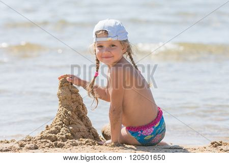 Five-year Girl In A Cap Sits On The Sand On The Beach And Building Sand Castle