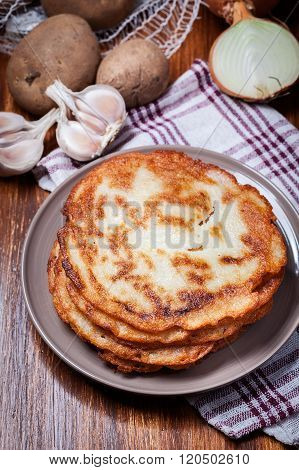 Stack Of Potato Pancakes On A Wooden Table. In The Background Po