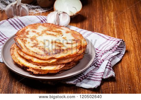 Stack Of Potato Pancakes On A Wooden Table. In The Background Potatoes