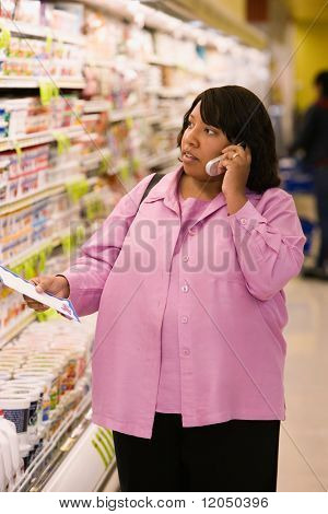 Woman on cell phone with grocery list in store