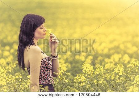 Genuine Woman In Meadow Of Yellow Flowers Sniffing Flower