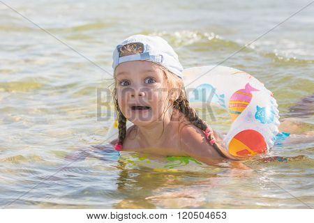 Funny Four-year Girl Floats With A Circle In The Water