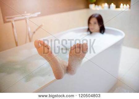Woman Taking Bath With Her Feet On The Edge Of The Bathtub