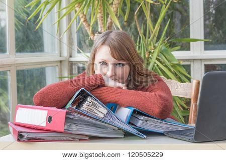 Young Woman Is Sitting At The Office Desk With Folders