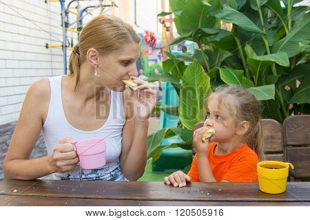 Mother And Daughter Looked At Each Other Having Breakfast On The Veranda
