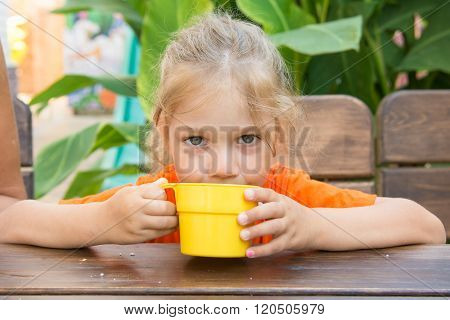 Four-year Girl Drinks A Drink From The Cup And Looks In The Frame