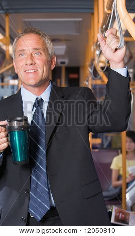 Mature businessman on subway with coffee