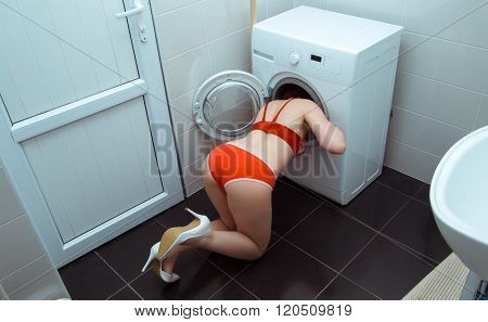girl in underwear in the bathroom putting head into washing machine
