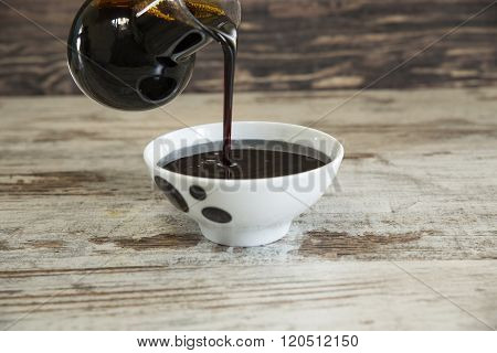 Grape molasses flowing from the glass pitcher on wooden background.