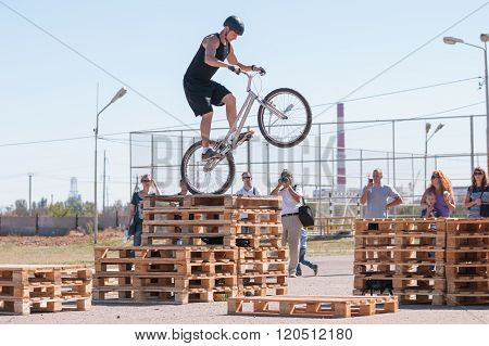 Cyclist Tracer Jumping On A Wooden Pallet In Front Of Audience