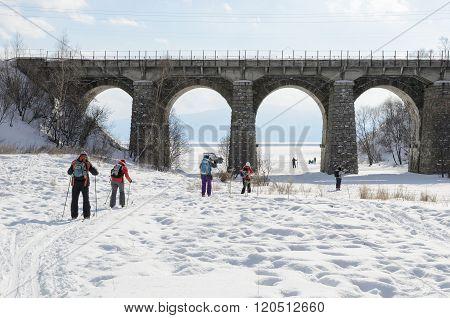 Irkutsk Region, Russia-Feb 27, 2016:Tourists-skiers go under Circum-Baikal Railway bridge