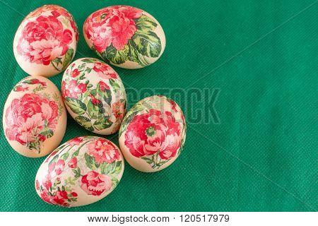 Decoupage decorated Easter eggs on green top view