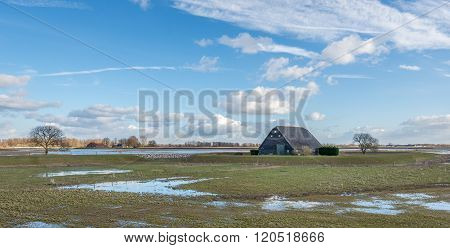 Old Black Painted Wooden Barn Surrounded By A Dike