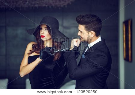 Sexy Woman In Hat Holding Young Rich Lover On Handcuffs