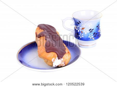 One Fresh Eclair On Blue Plate  With Coffe Cups