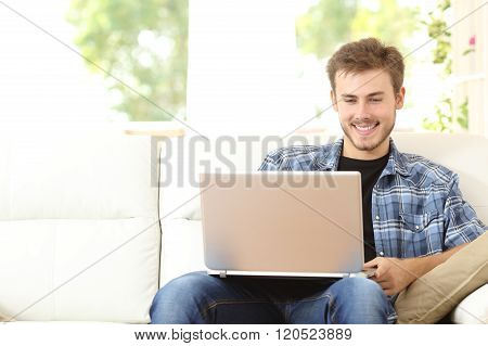 Man Using A Laptop Sitting On Couch At Home
