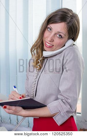 Young Businesswoman With Notebook On The Phone