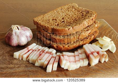 Sliced Bacon Of Salty Pork On A Chopping Board With Garlic And Bread