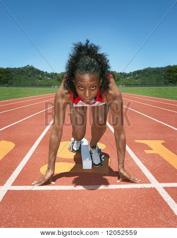 Female track athlete poised at starting line