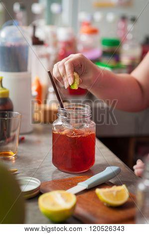 The process of making Thai lemon tea. Woman right hand squeeze lemon into cold tea