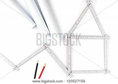 White Meter Tool Forming A House, Two Drawing Pencils And Paper  Drawings On White Background