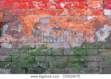 Half weathered brick wall painted in red and orange