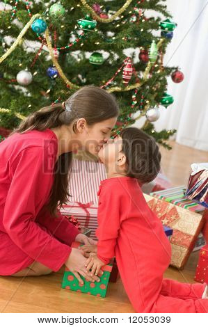 Sister and brother kissing on Christmas day