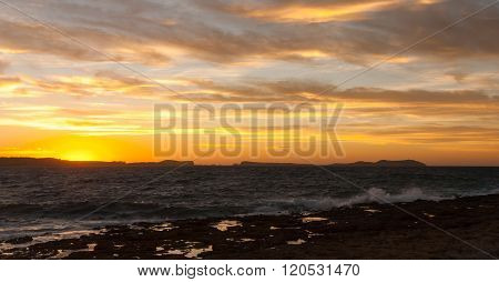 Golden sunset behind Conejera Islands.  Choppy waters of Balearic sea churns waves on rocks along sh